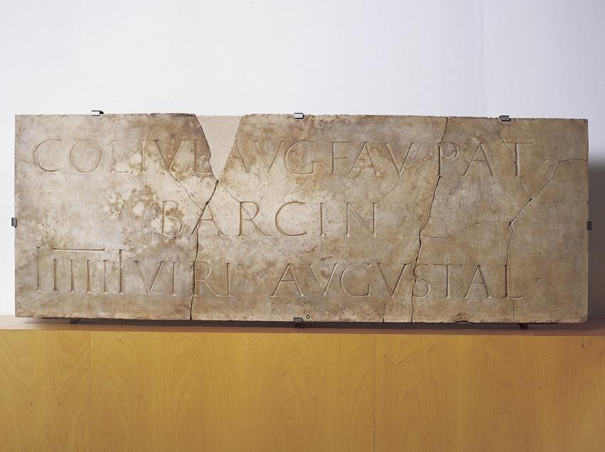 Inscripció dedicada a la ciutat, on apareix el nom de Barcino (segle II d.C.), procedent de la plaça de Sant Miquel. Museu d'Història de la Ciutat.  (Imagen M.A.S.)