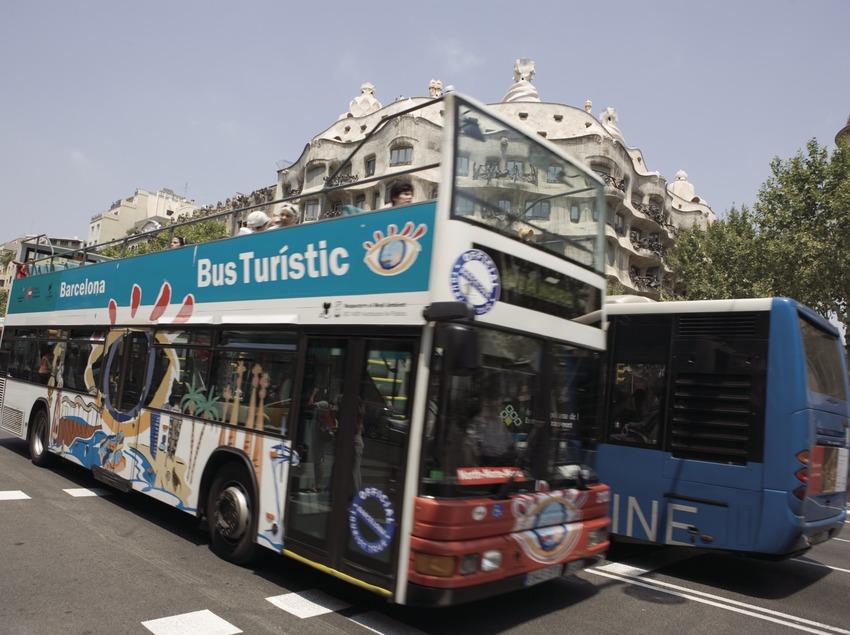 Autobús turístico a su paso por la Casa Milà, La Pedrera, en el Passeig de Gràcia.  (Nano Cañas)