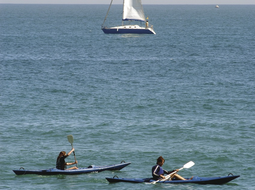Canoas y velero delante de la playa de la Barceloneta