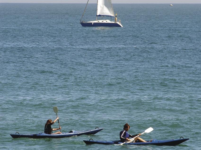 Kanus und Segelboot vor dem Strand von Barceloneta.