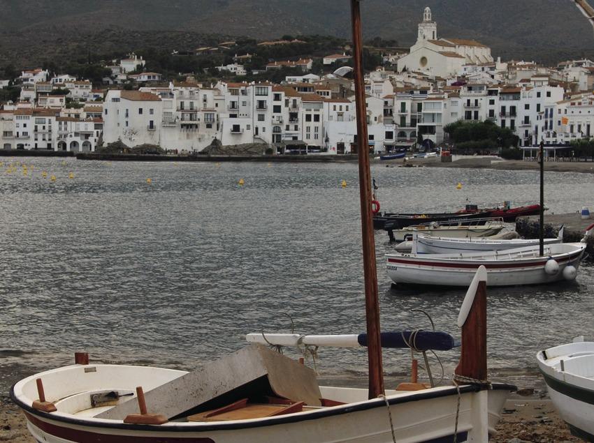 Barca a la platja amb el casc antic al fons.