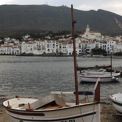 Barque sur la plage avec la vieille ville au fond.